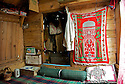 A Muslim carpet hangs on one of the wooden walls of a houseboat. Interiors are humble and with minimal furniture. All activities happen on the floor.