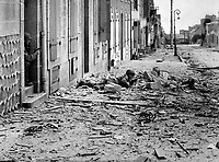 Americans take shelter during mop-up of Brest.  Crouching behind a pile of rubble, a U.S. soldier watches for German snipers in the streets of Brest, while a companion covers him from behind a doorway.  September 1944.  INP.  (OWI)<br /> Exact Date Shot Unknown<br /> NARA FILE #:  208-AA-19Z-1<br /> WAR &amp; CONFLICT BOOK #:  1054