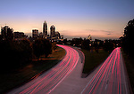 A photo of the Charlotte NC skyline at dusk, with the highway traffic speeding by, blurred by the long exposure. This is a favorite angle to get a photo of the Charlotte NC skyline, and the color from the setting sun behind the city really sets this one off.