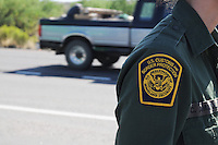 Nogales, Arizona - U.S. Customs Border Protection (CBP) Public Affairs Officer Crystal Amarillas (only her badge showing in this image) talks to journalists in an area next to a Border Patrol checkpoint on Interstate 19, in Nogales, Arizona. National and international reporters participated in a two-day event organized by the Border Patrol. Border Patrol checkpoints serve as inspection stations to detect illegal immigration and drug smuggling. Border Patrol agents assigned to fixed traffic checkpoints have wide discretion to stop vehicles for brief questioning and inspection of its occupants and its contents. This checkpoint is part of the Border Patrol Tucson Sector. Agent Photo by Eduardo © 2012