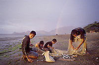 July 30th 2003-Dili, East Timor-Timorese men collect fish from the beach, in the Bidau area of Dili, shortly after dragging their fishing net from the sea, while a rainbow adorns the sky behind them. Photograph by Daniel J. Groshong/Tayo Photo Group .
