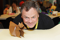 New York, NY, USA - June 23, 2012: Dennis Walker, from Scotland, posing with Hideo Komatsu's Squirrel at the OrigamiUSA 2012 convention held at Fashion Institute of Technology in New York City. Walker was guest of honor at the event and taught a class on how to fold this squirrel model.