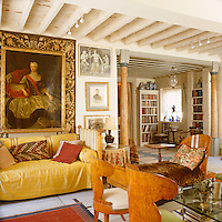 In this London living/dining room a sofa is covered in saffron-yellow and a large gilt-framed portrait creates a note of warmth