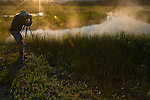 Nature Photographer photographing steam rising from river at sunrise in Yellowstone National Park, Wyoming, June