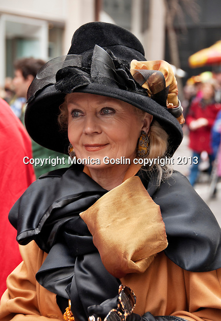 A woman wears a gold and black outfit and hat to the Easter Parade in New York City on Fifth Avenue