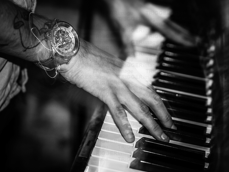 Hands playing piano in bar