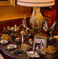A collection of silver animals and bowls is displayed on a side table covered in tapestry