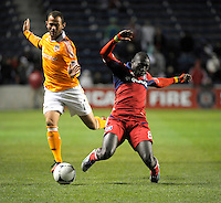 Houston midfielder Brad Davis (11) trips Chicago forward Dominic Oduro (8).  The Houston Dynamo defeated the Chicago Fire 2-1 in the Eastern Conference play-in game for the MLS Playoffs at Toyota Park in Bridgeview, IL on October 31, 2012.
