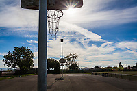 An urban park's basketball court under a blue sky with brush-strokes of clouds, a sunburst and a hoop with a chain link net.