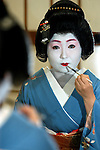 A Japanese geisha, who goes by the name of Norie, applies makeup in preparation for work in Tokyo, Japan.