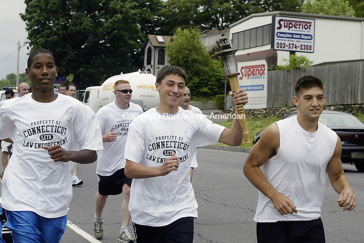 WATERBURY, CT -05 JUNE 2008 -060508DA02- Eric Demmons, carries the Special Olympic tourch after recieving it from the Waterbury police officials on Wolcott Road Thursday along side of Demmons, Josh Booth, left, and Joe Golden, right. The three boys all of Wolcott High School Track Team.  The 2008 Torch Run will cover over 539 miles and run through more than 100 cities and towns. Over 1,500 Law Enforcement officers and Special Olympics Athletes will participate in this year's Torch Run. The goal for 2008 is to raise $500,000 for Special Olympics Connecticut.<br /> In the last 21 years, the Connecticut Law Enforcement Torch Run has grown into the largest grass roots fund-raising event for Special Olympics. The 2008 Torch Run will cover over 539 miles and run through more than 100 cities and towns. Over 1,500 Law Enforcement officers and Special Olympics Athletes will participate in this year's Torch Run. These officers represent local, state, and federal departments, agencies and correctional facilities. The goal for 2008 is to raise $500,000 for Special Olympics Connecticut.<br /> Darlene Douty/Republican-American