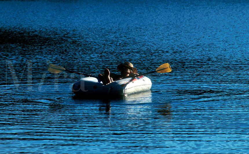 SENIOR MAN FLOATING IN A RAFT ON A LAKE. Cape Cod, MA