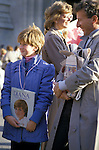A young girls awaits the arrival of Diana Princess of Wales displaying both a hair style and a book showing her devotion.