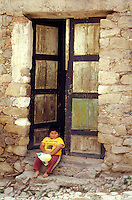 Plump Mexican boy sitting on a doorstep in the 19th-century silver-mining town of Real de Catorce, San Luis Potosi state, Mexico. Real de Catorce became a virtual ghost town during the early part of the 20th century. It has recently become a popuar destination for travellers.