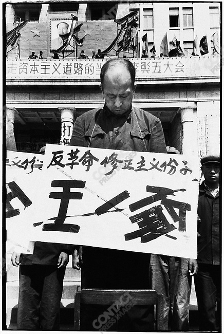 """Forced to stand on chairs in front of the North Plaza Hotel, the seven secretaries of the Heilongjiang Party committee are denounced for """"carrying out Liu Shaoqi's revisionist line."""" Each wears a placard with his name crossed out and a description of his alleged crime. Here, Wang Yilun. Harbin, 27 April 1967"""