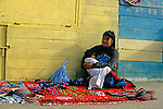 North America, Mexico, Baja California, Ensenada.  A woman and her baby await tourists to buy handmade trinkets.