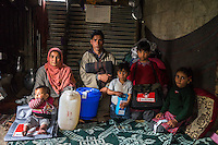 L-R: Zainab, 10 months, Shugufta, 29, Shugufta's husband, Azra, 5, Igra, 8, and Muzamil, 6, sit with the relief items in their temporary shelter in Narbal village, Jammu and Kashmir, India, on 24th March 2015. When the floods hit in the middle of the night, Shugufta and her family had to walk 5 miles to find shelter. Save the Children supported the family with shelter kits, blankets, hygiene items, food and tarpaulin, which they have used to build a temporary shelter next to their crumbled home. Photo by Suzanne Lee for Save the Children