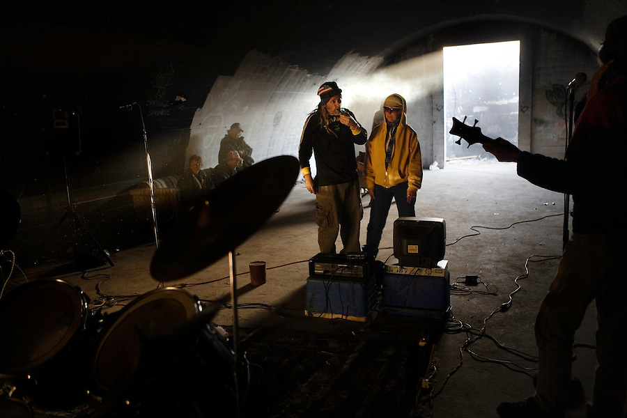Niland, Calif., February 15, 2008 ? Air Racket guitarist, Chance Holmes, center left, takes a hit from his marijuana pipe, while his girlfriend, Charlene Gavin waits her turn inside one of the bunkers at Slab City. The band decided to throw a party inside the bunker to avoid the storm outside. .