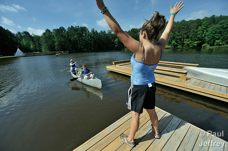 A canoe with two counselors and a camper gets waved toward the dock by Ali Miller, the summer supervisor at Camp Aldersgate in Little Rock, Arkansas. The camp, supported by United Methodist Women, offers children suffering from a variety of disabilities a safe experience similar to that which normally-abled children often enjoy.