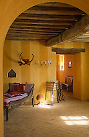 Small patches of sunlight dance on the terracotta tiled floor of this room furnished with a boat-like chaise-longue