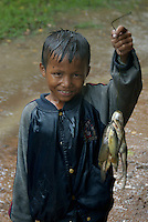 CAMBODIA 2007, BENG MEALEA TEMPLE, BOY IN POURING RAIN WITH FISH AND FROGS