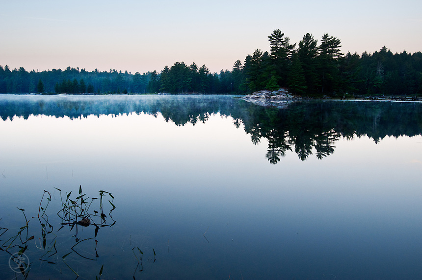 Mists rising from the surface of the mirror-still Balsam Lake in the blue light just before dawn, Killarney Provincial Park, Ontario.