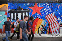 People walking past a section of the Berlin Wall depicting the painting Doin It Cool For The East Side by Jim Avignon, damaged by graffiti, part of the East Side Gallery, a 1.3km long section of the Wall on Muhlenstrasse painted in 1990 on its Eastern side by 105 artists from around the world, Berlin, Germany. Picture by Manuel Cohen