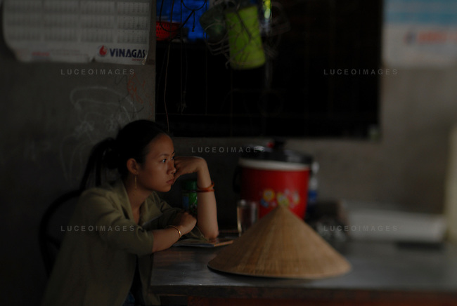 A Vietnamese woman waits out a rain storm at a restaurant outside of Ho Chi Minh City, Vietnam.