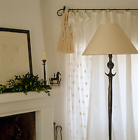A Giacometti standard lamp against a window dressed with sheer curtains