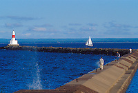 Tourists walk the upper harbor breakwater in Marquette, Mich. as a sailboat leaves the harbor past the breakwater light.
