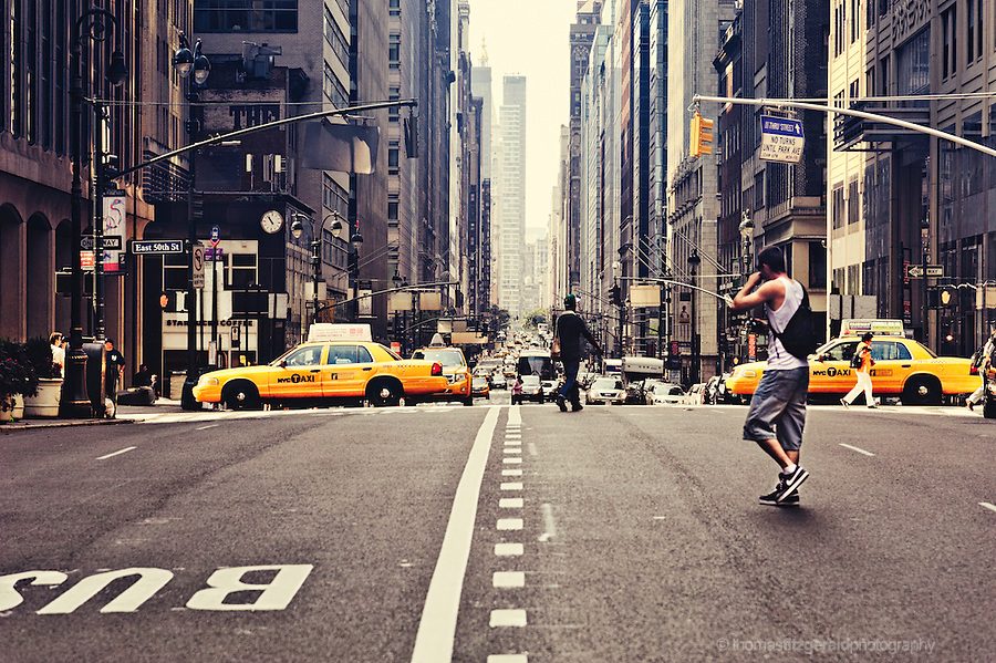 A man crosses a busy street in New York City