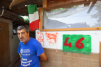 Italy. Lazio region. Rome. Tor di Quinto area. Gypsy camp. .A gypsy man, romanian citizen, is standing in front of his wooden shack. The hut has a number: forty six. Italian flag. He lives permanently as an immigrant in Italy. The Romani, who are known collectively in the Romani language as Romane or Rromane (depending on the dialect concerned) and also as Romany, Romanies, Romanis, Roma, Romsor or Rroms, are an ethnic group living mostly in Europe. Romanian immigration. 29.09.2011 © 2011 Didier Ruef