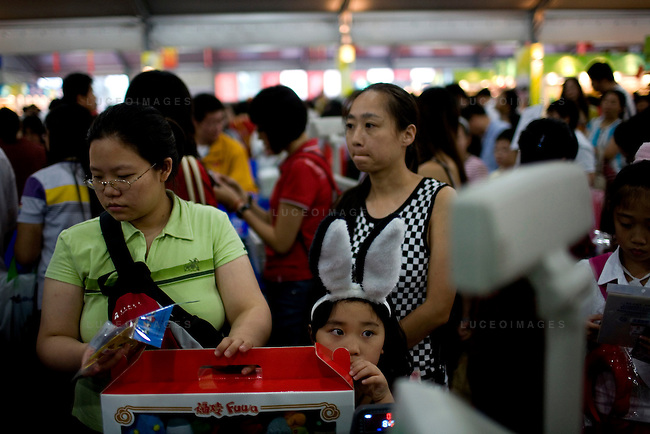 A family waits in line to make their purchase Olympics paraphernalia at the Superstore on the Olympic Green in Beijing, China on Thursday, August 21, 2008.  Kevin German