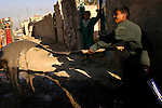 A boy in the Taric district of the Sadr City neighborhood in Baghdad shovels raw sewage into the street. The sewage seeps into leaky water pipes, contaminating the area's drinking supply.