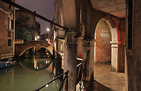 Narrow canal with bridges reflected in the water at night, Venice, Italy. The city of Venice is an archipelago of 117 small islands separated by canals and linked by bridges, in the Venetian Lagoon. The historical centre of Venice is listed as a UNESCO World Heritage Site. Picture by Manuel Cohen