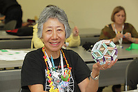 Student learning a modular origami design, Flexiball, created and taught by Jorge Pardo, Spain.