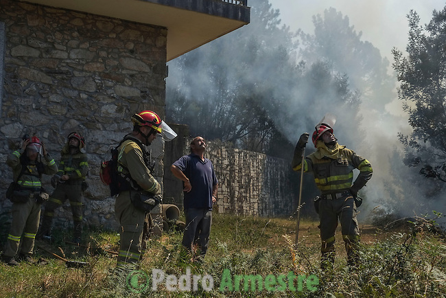 A firefighter (R) works at the site of a wildfire in Molinos de O Folon, (O Rosal) near Pontevedra, on August 29, 2013. Spain is prone to forest fires in summer because of soaring temperatures, strong winds and dry vegetation. Last year wildfires destroyed some 150,000 hectares of land in Spain from January to July, after one of the driest winters on record. © Pedro ARMESTRE