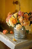 Garden roses are arranged in a small aluminium bucket