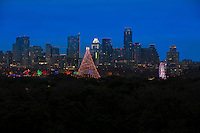 The Zilker Holiday Tree and Ferris Wheel at the Zilker Trail of Lights shines bright amid the Austin Skyline in Zilker Park, Austin, Texas.