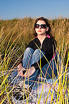 Young adult woman watching sunset at beach with sunglasses on