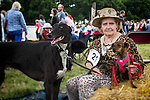 Elderly lady wearing leopard skin summer clothing with her two dogs at Helmingham Hall Dog Show
