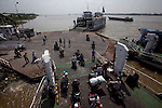 "Passengers board ferries to cross the Hau Giang River, a tributary of the Mekong River, in Long Xuyen, the capital of An Giang Province, Vietnam. When the Mekong River reaches Vietnam it splits into two smaller riveres. The ""Tien Giang"", which means ""upper river"" and the ""Hau Giang"", which means ""lower river"". Photo taken on Monday, December 8, 2009. Kevin German / Luceo Images"