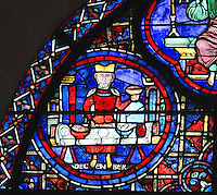 At the end of the year, a wealthy man sits at a table to enjoy the fruits of the year's labour. He has a good meal of fish, meat and wine, with wafers to remind us of the eucharist and of giving thanks to God, section of December from the Zodiac and the labours of the months stained glass window, 1217, in the ambulatory of Chartres Cathedral, Eure-et-Loir, France. This calendar window contains scenes showing the zodiacal symbol with its corresponding monthly activity. Chartres cathedral was built 1194-1250 and is a fine example of Gothic architecture. Most of its windows date from 1205-40 although a few earlier 12th century examples are also intact. It was declared a UNESCO World Heritage Site in 1979. Picture by Manuel Cohen