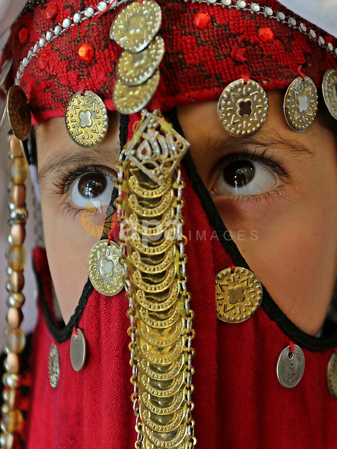 A Palestinian girl wears heritage as she poses for a photograph during a ceremony, in Gaza City April 20, 2017. Photo by Ashraf Amra