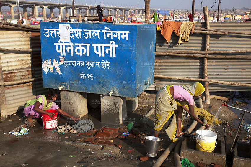India. Uttar Pradesh state. Allahabad. Maha Kumbh Mela. An indian woman is making a laundry while another is pouring water in a bucket. Both women wear sarees. On a the blue water tank, it is writen in Hindi language: Uttar Pradesh (abbreviated U.P.) Water Corporation. Drinking water. Pleasedon't leave the tap open. The Kumbh Mela, believed to be the largest religious gathering is held every 12 years on the banks of the 'Sangam'- the confluence of the holy rivers Ganga, Yamuna and the mythical Saraswati. The belief is that bathing and taking a holy dip will wash and free one from all the past sins, get salvation and paves the way for Moksha (meaning liberation from the cycle of Life, Death and Rebirth). The Maha (great) Kumbh Mela, which comes after 12 Purna Kumbh Mela, or 144 years, is always held at Allahabad. Uttar Pradesh (abbreviated U.P.) is a state located in northern India. 13.02.13 © 2013 Didier Ruef