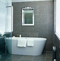 A Venetian glass mirror hangs on the wall above the bath in this grey slate tiled bathroom