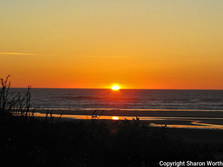A setting sun and its reflection immerse Haceta Beach in a golden glow.