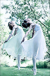 Two female ballet dancers wearing white dresses standing on point outdoors