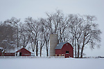 Idaho, South Central, Twin Falls, A farm scene with red barn and silo on a snowy, overcast winter day.