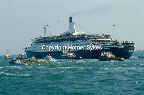 Falklands War. Queen Elizabeth QE2 leaves from Southampton for the Falklands Conflict. May 1982 Flotilia of boats see her on her way. England.
